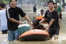 Residents evacuate their homes in a flooded village in Marikina City