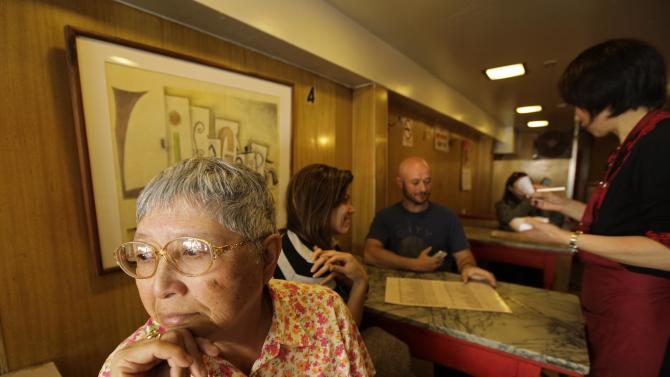 "Darlene Lee, 71, looks out the window after ordering lunch one last time from waitress Fanny He, right, at the Sam Wo restaurant in San Francisco, Friday, April 20, 2012. Lee has been coming to the restaurant for over 60 years since she was a girl growing up in Chinatown. The 100-year-old Chinese restaurant known for having ""the world's rudest waiter"" is shutting its doors and serving its last customers Friday. (AP Photo/Eric Risberg)"