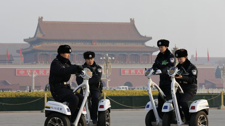 Police officers ride motorised vehicles at Tiananmen Square prior to a plenary session of the National People's Congress in Beijing