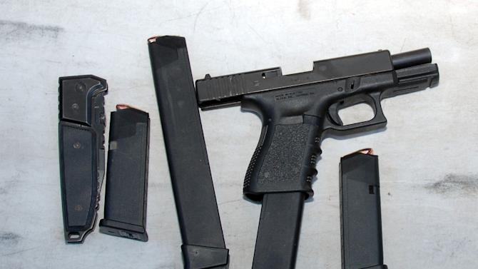 In this image released by the Pima County Sheriff's department, weapons including a gun, magazines and a knive are seen in the aftermath of the Tucson shooting rampage that killed six people and wounded former U.S. Rep. Gabrielle Giffords and 12 others in January 2011.  Authorities released more than 300 photos on Tuesday, May 21, 2013, made by investigators during their investigation in the parking lot of the shopping center where the shooting took place.  (AP Photo/Pima County Sheriff)