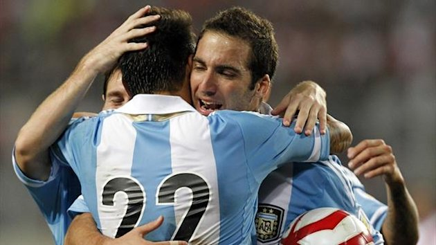 Agentina&#39;s Gonzalo Higuain (R) is embraced by team-ates Ezequiel Lavezzi (22) and Lionel Messi after he scored a goal against Peru during their 2014 World Cup qualifier (Reuters)