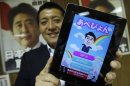 "Hirai, Director of Internet Media Division of Japan's ruling LDP, poses with an iPad displaying ""Abe Pyon"", LDP's official game app featuring Japan's PM Abe, in Tokyo"