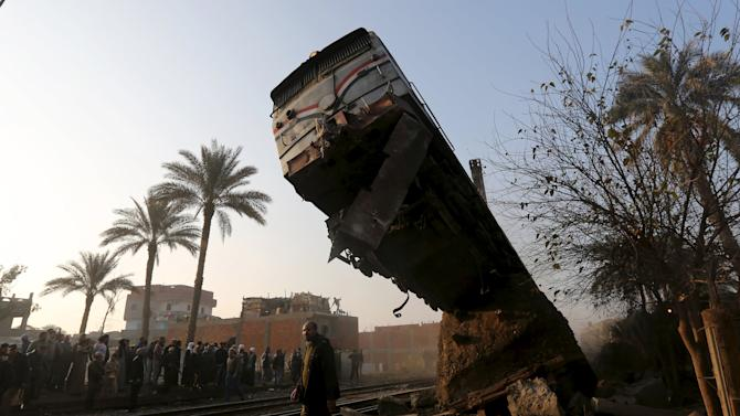 A crowd looks at the wreckage of a train crash in Beni Suef, south of Cairo