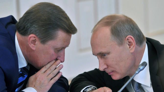 FILE - In this file photo taken on Tuesday, Nov. 6, 2012, Russian President Vladimir Putin, right, listens to  Kremlin's Chief of Staff Sergei Ivanov during a meeting at the Novo-Ogaryovo residence outside Moscow. Ivanov said Sunday Nov. 11, 2012 he was aware of alleged embezzlement of state funds by officials in a company developing Russia's satellite navigation system for several years, but didn't speak publicly about it for several years to prevent the culprits from covering up their deeds.  (AP Photo/RIA Novosti, Alexei Nikolsky, Presidential Press Service)