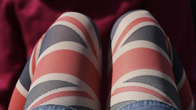 A fan wearing leggings marked with the stripes of Great Britain's flag rests on the grass at the rowing venue in Eton Dorney, near Windsor, England, at the 2012 Summer Olympics, Monday, July 30, 2012. (AP Photo/Natacha Pisarenko)