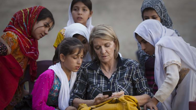 FILE - In this Saturday, Oct. 1, 2011 file photo, Associated Press Special Regional Correspondent for Afghanistan and Pakistan Kathy Gannon sits with girls at a school in Kandahar, Afghanistan. A Kabul court announced Wednesday, July 23, 2014 that the Afghan police officer charged with killing Associated Press photographer Anja Niedringhaus and wounding veteran AP correspondent Kathy Gannon has been convicted and sentenced to death.(AP Photo/Anja Niedringhaus, File)