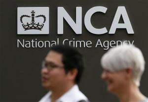 Pedestrians walk past the National Crime Agency headquarters in London