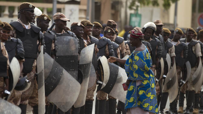 A woman talks with security forces providing security for a march in support of a recent military coup, in Bamako, Mali Wednesday, March 28, 2012. The body representing nations in western Africa has suspended Mali and has put a peacekeeping force on standby in the most direct threat yet to the junta that seized control of this nation in a coup last week.(AP Photo/Rebecca Blackwell)