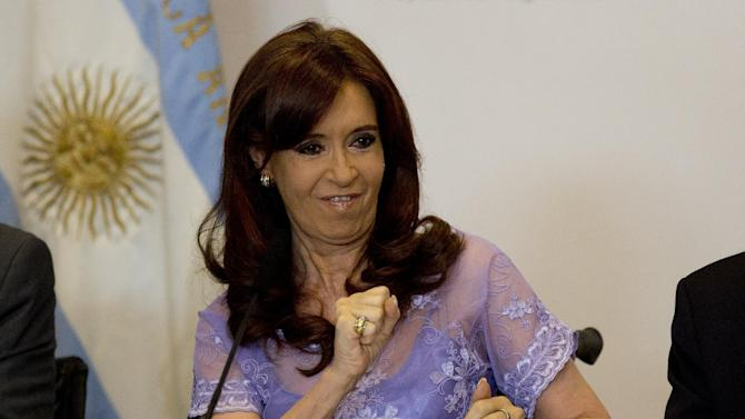Argentina's President Cristina Fernandez, sitting in a wheelchair, cheers at supporters at the Casa Rosada government palace during a signing ceremony in Buenos Aires, Argentina, Friday, Jan. 30, 2015. Fernandez said Friday that she will voice all the opinions she wants to about the case of prosecutor Alberto Nisman, who was found dead on Jan. 18, hours before he was to elaborate on his accusation that Fernandez protected those responsible for a 1994 terror bombing. (AP Photo/Rodrigo Abd)