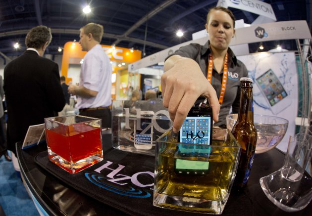 <p>               HZO representative Devin Markle pulls a smart phone out of a container of beer after demonstrating the company's WaterBlock technology at the Consumer Electronics Show, Wednesday, Jan. 9, 2013, in Las Vegas. WaterBlock is a nanobacking that coats the inner circuits of a device. (AP Photo/Julie Jacobson)