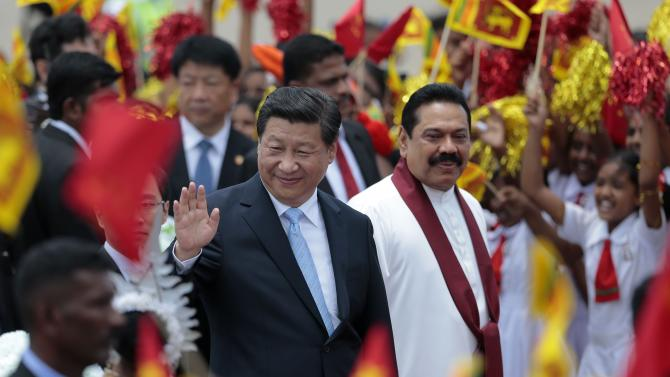 China's President Xi Jinping, left, waves to the gathering as he walks with Sri Lankan President Mahinda Rajapaksa upon arrival at the airport in Colombo, Sri Lanka, Tuesday, Sept. 16, 2014. (AP Photo/Eranga Jayawardena)