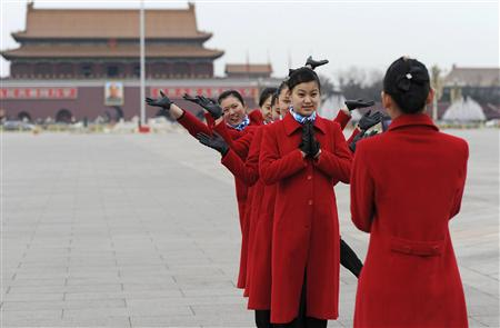 Hotel guides pose for a photograph at Tiananmen Square in Beijing