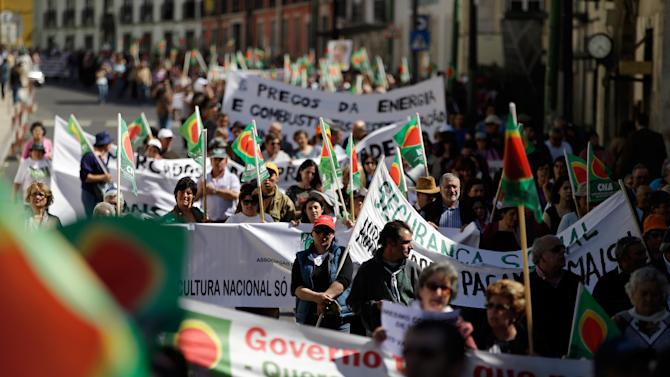 Farmers carry banners and flags during a protest march through downtown Lisbon Wednesday, April 17 2013. Thousands of farmers took part in the protest against the government's agriculture policy. (AP Photo/Armando Franca)