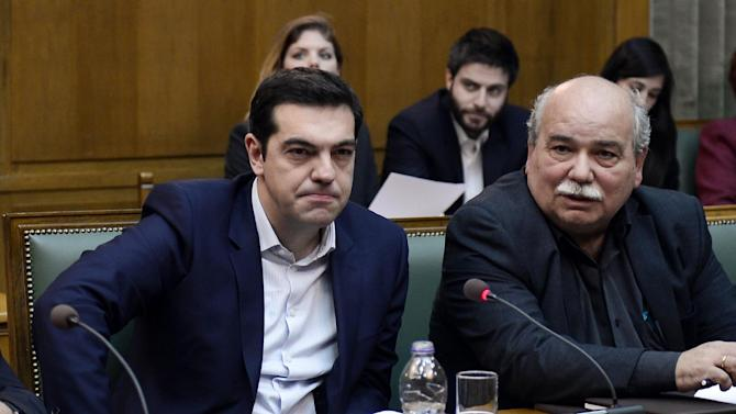Greece's radical new Prime Minister Alexis Tsipras (L) and Interior Minister Nikos Vroutsis attend the new government's first cabinet meeting on January 28, 2015 at the Greek Parliament in Athens