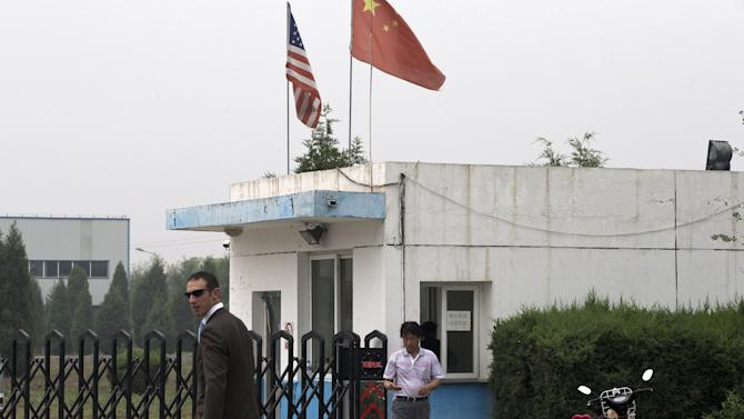 An unidentified U.S. Embassy employee, left, and Chinese official walk outside the closed gate at Specialty Medical Supplies plant where American Chip Starnes, co-owner of the plant, not in picture, is being held hostage at the Jinyurui Science and Technology Park in Qiao Zi township of Huairou District, on the outskirts of Beijing, China Monday, June 24, 2013. An American executive said Monday Starnes has been held hostage for four days at his medical supply plant in Beijing by dozens of workers demanding severance packages like those given to co-workers in a phased-out department. (AP Photo/Andy Wong)