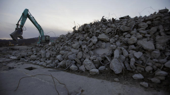 In this Friday, Feb. 22, 2013 photo, heavy machinery sorts out concrete and steel debris left after the March 11, 2011 earthquake and tsunami, at a scrap yard in Rikuzentakata, Iwate prefecture, northeastern Japan. About three-quarters of Rikuzentakata's 8,000-some homes were destroyed by the 13-meter (43-foot) tsunami that swept up to 4 kilometers (two and a half miles) up its wedge-shaped river valley. Most debris was hauled away long ago. The wind whips through derelict skeletons of the few concrete buildings yet to be demolished. Utility poles stud roadsides and empty lots littered with mundane odds and ends - kitchen strainers, skillets, laundry hangers, a rusted clock. (AP Photo/Junji Kurokawa)