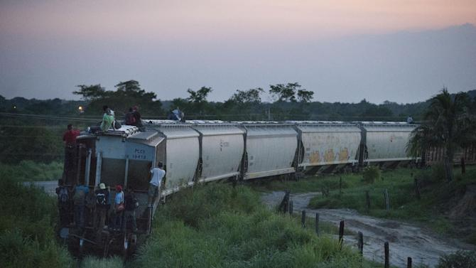 """In this Aug. 26, 2014 photo, a handful of Central American migrants cling to a northbound freight train after jumping aboard outside Arriaga, Mexico. A Mexican crackdown seems to be keeping women and children off the deadly train, known as """"The Beast,"""" that has traditionally helped thousands of migrants head north. (AP Photo/Rebecca Blackwell)"""