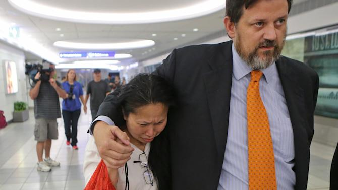 """Komdown """"Dow"""" Boyer leaves with her lawyer, Jim Wyrsch, on Monday evening, June 23, 2014, at Lambert International Airport, after returning from Chicago where she was almost deported to Thailand in St. Louis. Dow Boyer was almost deported to Thailand earlier Monday after her conviction for stealing from her employer in Farmington. (AP Photo/St. Louis Post-Dispatch, J.B. Forbes) EDWARDSVILLE INTELLIGENCER OUT; THE ALTON TELEGRAPH OUT"""