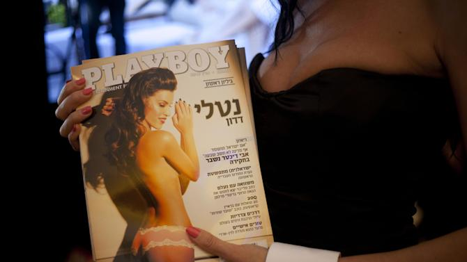 """A model dressed as a Playboy bunny poses with the first Hebrew language edition of the popular men's magazine in Tel Aviv, Israel, Tuesday, March 5, 2013. Israelis can now read Playboy """"for the articles."""" A U.S. emigre, Daniel Pomerantz, on Tuesday launched the first Hebrew language edition of the popular men's magazine. Playboy has been widely available in Israel for years, but this marks the first local edition of the magazine. It features Israeli models and articles by Israeli writers. It's not clear how well the magazine will be received in the Holy Land, where religious sensitivities simmer under the surface and observant Jews and Muslims live by strict modesty rules. Adult magazines and videos are freely available, but not with local models and not in Hebrew. Playboy was launched in 1953 with the iconic Marilyn Monroe centerfold. It peaked in popularity in the 1970's. Circulation has declined since the rise of adult Internet sites. (AP Photo/Ariel Schalit)"""