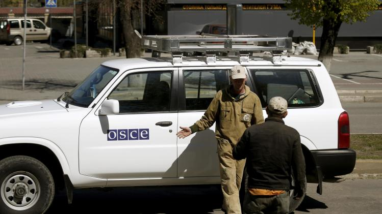 Municipal workers take a photo at an OSCE car near the seized office of the SBU state security service in Luhansk