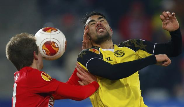 Freiburg's Immanuel Hoehn (L) and Sevilla's Vicente Iborra fight for the ball during their Europa League soccer match in Freiburg