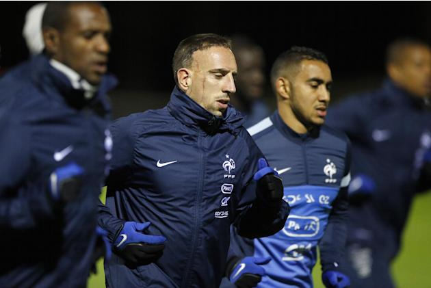 France's soccer forward Franck Ribery, center, runs with Eric Abidal, left, and Dimitri Payet, right, during a training session at Clairefontaine training center, south of Paris, Monday, Nov. 11, 2013