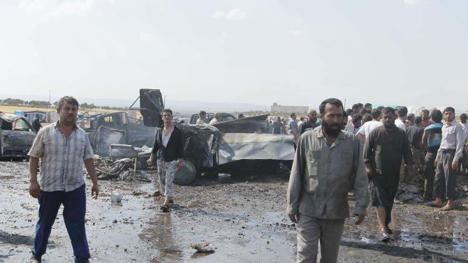 Men inspect the damage at a fuel market hit by a car bomb in the Maarat Al-Naasan area of Idlib