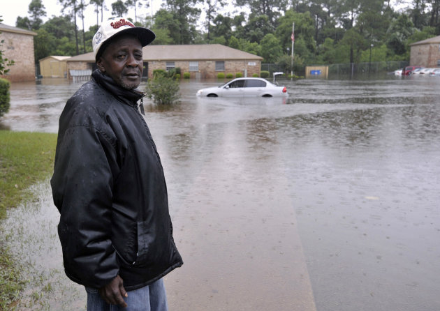 Forest Creek apartment resident Calvin Grace returns from checking on the flooding conditions in his unit Sunday, June 10, 2012, after receiving nearly two feet of water on Saturday, in Pensacola, Fla