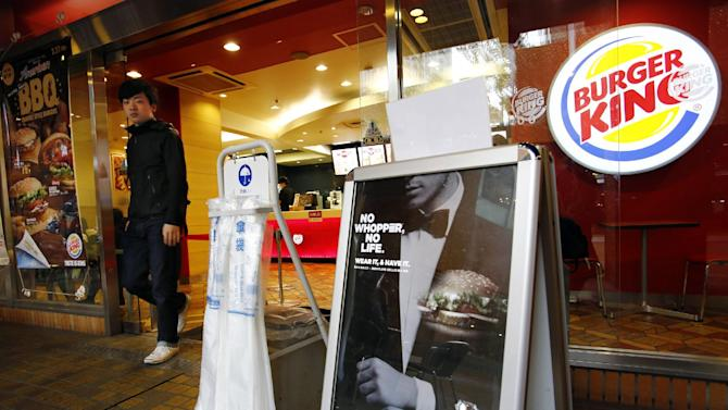 A customer leaves a Burger King fast-food restaurant in Tokyo, Wednesday, April 1, 2015. Burger King said last month that a special Whopper grilled beef burger-scented cologne will be sold on April 1 in Japan. (AP Photo/Shizuo Kambayashi)
