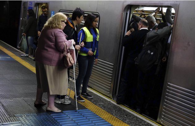 Visually impaired people wait for an available train, as they are accompanied by an assistant, at a subway station in downtown Sao Paulo