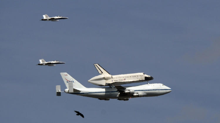 The Space Shuttle Endeavour atop a modified 747 flies followed by two chase planes and a bird as near Dodger Stadium, Friday, Sept. 21, 2012, in Los Angeles, on a sightseeing tour of California, the last aerial hurrah before retiring to a Los Angeles museum. (AP Photo/Mark J. Terrill)