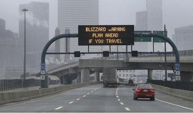 A warning sign flashes for motorists on the expressway into Boston as snow starts to fall on Friday, Feb. 8, 2013. A major winter storm is heading toward the U.S. Northeast with up to 2 feet of snow e