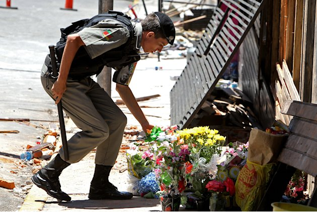 A police officer places flowers outside the Kiss nightclub that were brought by mourners in memory of those who died due to a fire at the club in Santa Maria, Brazil, Monday, Jan. 28, 2013.  A fast-mo