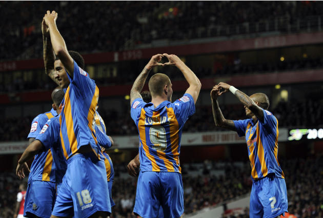 Shrewsbury Town's James Collins, center, celebrates after scoring against Arsenal  during their English League Cup soccer match at the Emirates stadium, London, Tuesday, Sept. 20, 2011. (AP Photo/Tom