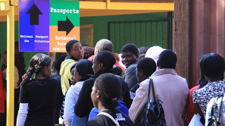 In this photo taken Monday, Aug. 5, 2014, Zimbabweans wait in a queue at the main passport office in Harare. People queue for hours before the offices open in the hope of securing a passport that will allow them to escape their country's dearth of opportunities and search for work abroad. (AP Photo/Tsvangirayi Mukwazhi)