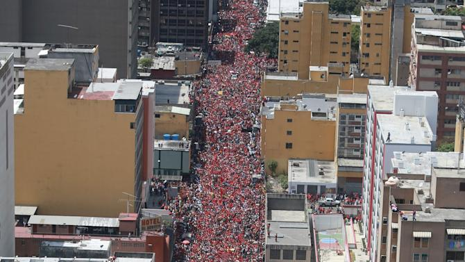 In this photo released by Miraflores Presidential Press Office, supporters of Venezuela's late President Hugo Chavez crowd the street, surrounding his coffin as it is paraded from the hospital, where he died on Tuesday, to a military academy where his body will lie in state in Caracas, Venezuela, Wednesday, March 6, 2013. Seven days of mourning were declared, all schools were suspended for the week and friendly heads of state were expected for an elaborate funeral Friday. (AP Photo/Miraflores Presidential Press Office)