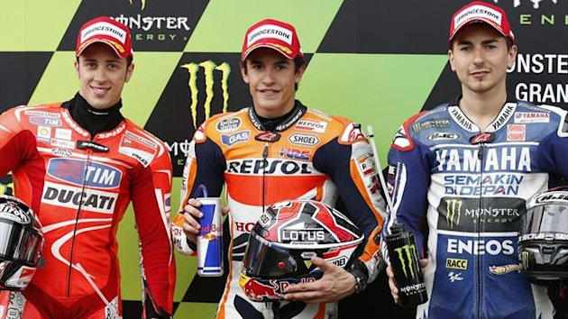 Honda's Marc Marquez (C) of Spain stands between Yamaha MotoGP rider Jorge Lorenzo (R) of Spain and Ducati MotoGP rider Andrea Dovizioso (L) of Italy after taking the pole position during the French Grand Prix in Le Mans circuit (Reuters)