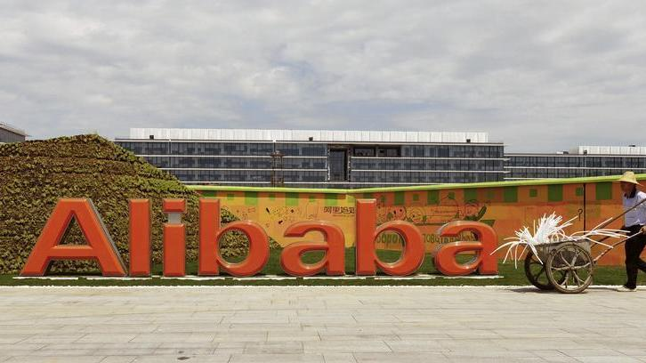 A worker walks past a logo of Alibaba Group at its headquarters on the outskirts of Hangzhou