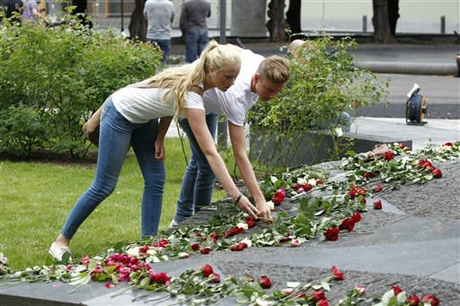 Two young people lay down flowers outside the damaged main government building in Oslo, Norway, Sunday, July 22, 2012. Norway on Sunday paused to commemorate the 77 victims of a bomb and gun massacre that shocked the peaceful nation one year ago, a tragedy that the prime minister said had brought Norwegians together in defense of democracy and tolerance. (AP Photo/Schroeder, Tor Erik/NTB scanpix)