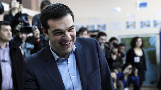 Alexis Tsipras, leader of Greece's Syriza left-wing main opposition party laughs as he arrives to cast his vote at a polling station in Athens, Sunday, Jan. 25, 2015. Greeks were voting Sunday in an early general election crucial for the country's financial future, with the radical left Syriza party of Alexis Tsipras tipped as the favorite to win, although possibly without a large enough majority to form a government. (AP Photo/Lefteris Pitarakis)