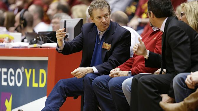 U.S. Sen. Rand Paul, R-Ky., left, talks to fans during the first half of an NCAA college basketball game between Iowa State and Texas Tech, Saturday, Feb. 7, 2015, in Ames, Iowa. (AP Photo/Charlie Neibergall)