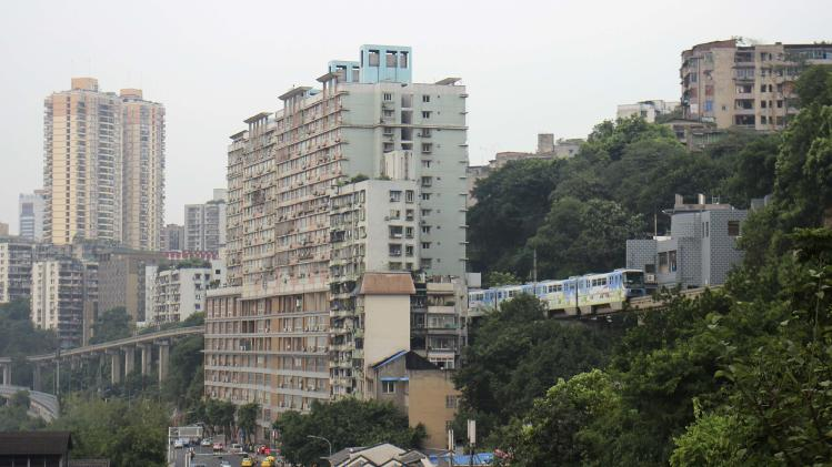 A train of subway line 2 runs through a residential building in Chongqing Municipality