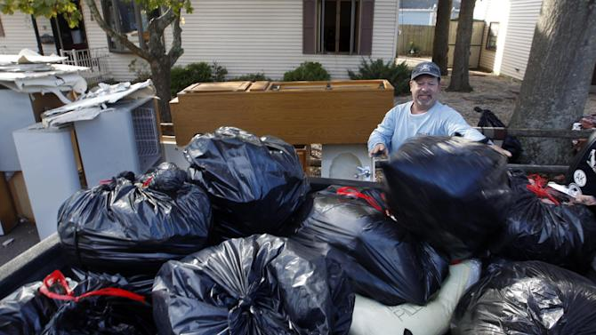 Bill Klipp, of Florida works on cleaning out his father's flood damaged home Tuesday, Nov. 6, 2012, in Brick, N.J. Brick is ordering mandatory evacuations in advance of an approaching nor'easter and in the wake of Superstorm Sandy. (AP Photo/Mel Evans)