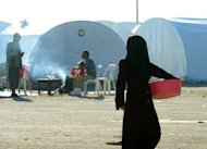 A woman walks past tents at a refugee camp close to the northern town of Azaz on the Syrian-Turkish border. Air raids, clashes and car bombings shook Syria on Sunday, killing nearly 100 people, monitors said, as world powers look to pick up the pieces of a failed bid to bring in a Muslim holiday ceasefire