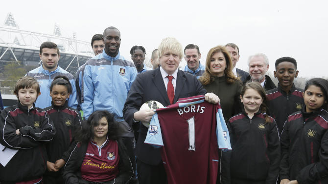 Mayor ff London Boris Johnson, centre, with Karen Brady, vice chairman of   English Premier League soccer team West Ham United, centre right, , pose for the media as the mayor holds a West Ham soccer jersey on a balcony overlooking the London 2012 Olympic summer games stadium London, Friday, March, 22, 2013. The stadium built for the summer games has had its future secured in a deal where a local English Premier League team West Ham United will have a 99 year lease to use the stadium starting in 2016, it was announced at a press conference in  (AP Photo/Alastair Grant)