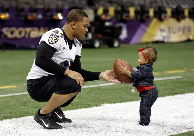 Ray Rice hands a football to his daughter, Rayven, during Saturdays informal practice. (AP)