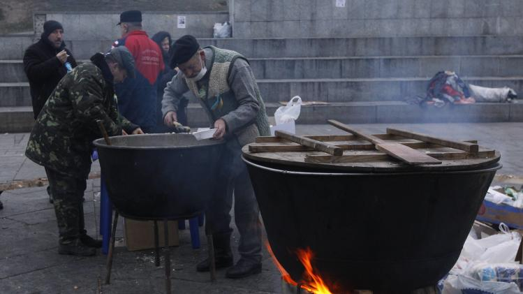People eat in the early morning, next to cooking stations set up near the Ukrainian cabinet of ministers building, during a rally to support EU integration in Kiev