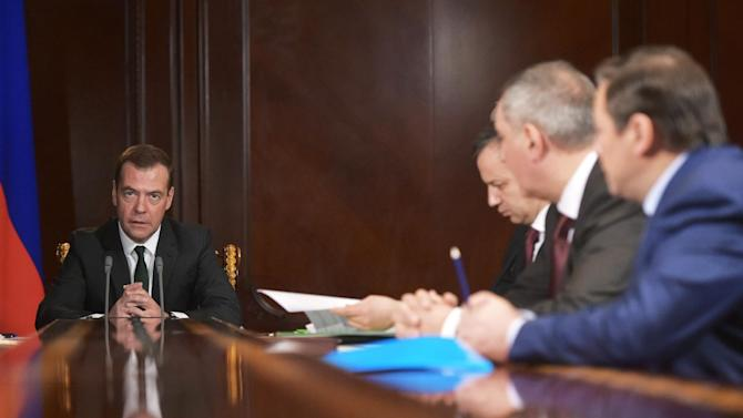Russian Prime Minister Dmitry Medvedev, left, holds a meeting on the situation in banking in the Gorki residence, outside Moscow, Russia, Monday, Feb.  8, 2016. The Central Bank pulled the license for Interkommerzbank, saying there was a significant imbalance between the assets and liabilities of the country's 67th largest bank. It also withdrew the license of the country's 186th largest bank, Alta Bank, on the grounds that it was unable to meet creditors' claims.(Alexander Astafyev/Sputnik, Government Press Service Pool Photo via AP)
