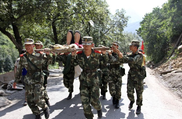 Soldiers carry an injured person with a stretcher towards safer area after two earthquakes hit Zhaotong, Yunnan province, September 7, 2012.