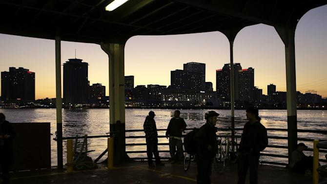 People ride the ferry boat across the Mississippi from downtown New Orleans, seen in background, to Algiers Point, Tuesday, Jan. 15, 2013. A boat ride is one of the best ways to get a look at the New Orleans skyline and the Mississippi River's daily parade of river barges, steamships and cruise ships. The Algiers Point ferry, which has been in operation since the early 1800s, is free to pedestrians.  (AP Photo/Gerald Herbert)